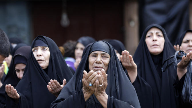 Shiite Muslim women pray during a mourning procession to mark the Muslim festival of Ashoura, an important period of mourning for Shiites in Karbala, 50 miles (80 kilometers) south of Baghdad, Iraq, Saturday Nov. 24, 2012. The festival of Ashoura commemorates the martyrdom of Imam Hussein, the grandson of Prophet Muhammad at the Battle of Karbala, Iraq, in the year A.D. 680. (AP Photo / Khalid Mohammed)