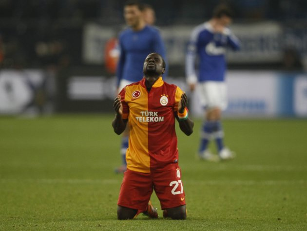Galatasaray's Eboue prays on the pitch following his team's victory over Schalke 04 in their Champions League soccer match in Gelsenkirchen