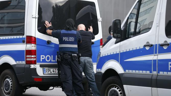 Armed masked police officers detain suspect following an early morning raid at 'Cargo City' in Frankfurt airport