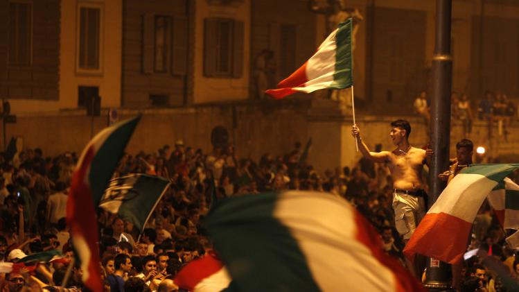 Italian soccer fans celebrate after Italy's 2-1 victory over Germany in the Euro 2012 soccer championship semifinal match, in Rome's Piazza del Popolo square, Thursday, June 28, 2012. (AP Photo/Alessandra Tarantino)