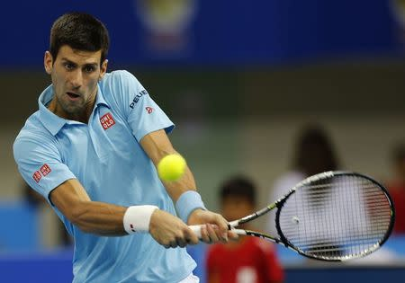 UAE Royals' Novak Djokovic of Serbia hits a return to Indian Aces' Gael Monfis of France during their match at the International Premier Tennis League in Dubai