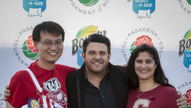 "IMAGE DISTRIBUTED FOR BOUNTY - Travel Channel's Adam Richman and contestants, Chao Qi, left, and Nancy Valenzuela, right, compete to see who will be crowned the Bounty-Select-A-Size ""Tastiest Tailgate Mess""  cook-off champion at the 2013 Rose Bowl Game tailgate on Tuesday, Jan. 1, 2013, in Pasadena, Calif. (Bret Hartman/AP Images for Bounty)"