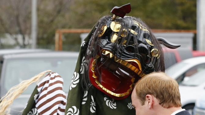 Britain's Prince William is greeted by a lion dancer as he visits Onagawa, Miyagi prefecture