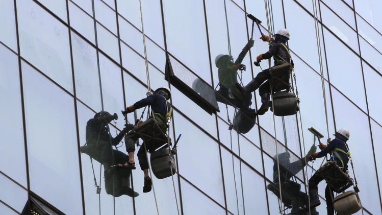 Workers clean windows of a building in Seoul, South Korea, Thursday, June 5, 2014. South Korea's economic growth hit its highest level in three years in the first quarter, boosted by new home construction and exports of electronics. (AP Photo/Ahn Young-joon)