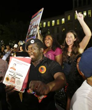 James Evan Muhammad, front left, of the New Black Panther Party, shouts slogans after the verdict of not guilty was handed down in the trial of George Zimmerman at the Seminole County Courthouse, Saturday, July 13, 2013, in Sanford, Fla. Neighborhood watch captain George Zimmerman was cleared of all charges Saturday in the shooting of Trayvon Martin, the unarmed black teenager whose killing unleashed furious debate across the U.S. over racial profiling, self-defense and equal justice. (AP Photo/John Raoux)