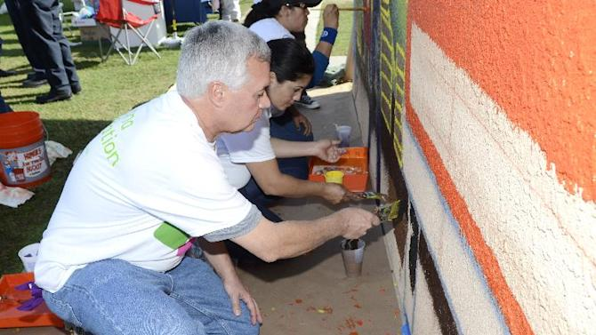 IMAGE DISTRIBUTED FOR HUMANA -Jeff Chicots, left, Regional V.P. of Medicare Sales for Humana, helps paint a community mural at the Las Casas Housing Development in Coachella, Calif, on Saturday, December 1, 2012. More than 200 volunteers joined The Humana Foundation, the philanthropic arm of Humana, Inc., one of the nation's leading health care companies; KaBOOM!, a national non-profit dedicated to saving play; the Family YMCA of the Desert, the largest provider of licensed childcare in the Coachella Valley; and the Coachella Valley Housing Coalition, an award-winning non-profit housing development corporation, to build a new multi-generational playground in just six hours. The playground build is one of many wellness-focused activities taking place leading up to the 2013 Humana Challenge golf tournament to be held Jan. 14-20, 2013, in La Quinta, Calif. The build is a direct result of the collective efforts of thousands of people who wore Humana pedometers and logged their steps during the 2012 Humana Challenge Walkit program. Every step counted toward the donation made by the Humana Foundation. (Rodrigo Pena / AP Images for Humana)