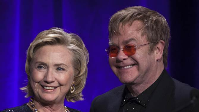 """Former Secretary of State Hillary Clinton, left, poses onstage for a photograph with Elton John after receiving her Founders award during the Elton John AIDS Foundation's 12th Annual """"An Enduring Vision"""" benefit gala at Cipriani Wall Street on Tuesday, Oct. 15, 2013, in New York. (Photo by Carlo Allegri/Invision/AP)"""