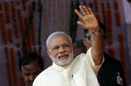 India's Prime Minister Narendra Modi waves towards his supporters during a rally in Mathura