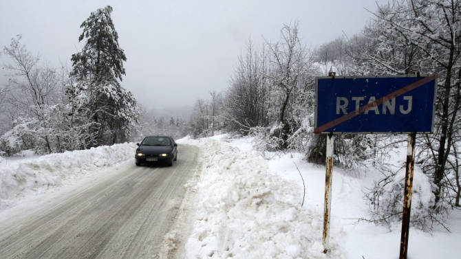 """A car past a traffic sign saying """"Rtanj"""" in the Serbian mountain of Rtanj, some 220km (140 miles) southeast of Belgrade, Serbia, Friday, Dec. 21, 2012. Though the Mayans never predicted outright that the world would end Friday, some New Agers are convinced that the apocalypse is indeed coming Dec. 21, 2012, the supposed end of a 5,125-year Mayan calendar. While descendants of the ancient Mayans in Mexico are facing the date with a calm conviction that life will go on, a frenzy has gripped others across the world, drawing them to several spots said to promise survival. Mayan doomsday cultists are flocking to Mount Rtanj, a pyramidal peak in Serbia, which they believe may have the power to save them on December 21.(AP Photo/Darko Vojinovic)"""