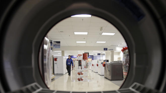 FILE - In this Dec. 6, 2012, photo, an employee walks through the appliance department at a Sears in North Olmsted, Ohio.  Sears posted a smaller loss in the fourth quarter as it reduced its inventory and expenses while sales at its namesake stores rose slightly.   (AP Photo/Mark Duncan, File)