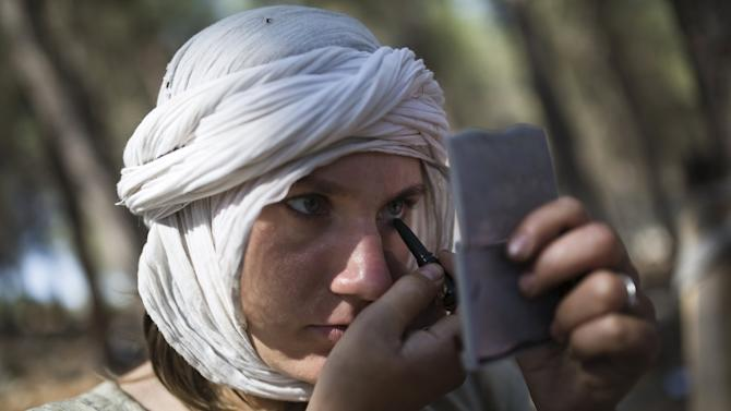 An enthusiast wearing a costume applies eyeliner during a re-enactment of a Crusaders battle in Israel's Galilee region