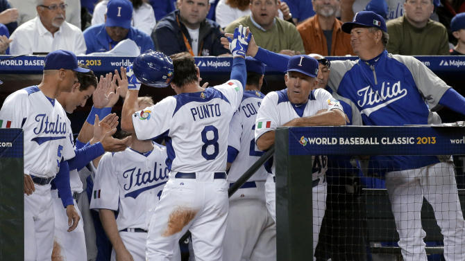 Italy's Nick Punto (8) celebrates as he enters the dugout after scoring on a wild pitch during the first inning of a World Baseball Classic game against the United States on Saturday, March 9, 2013, in Phoenix. (AP Photo/Charlie Riedel)