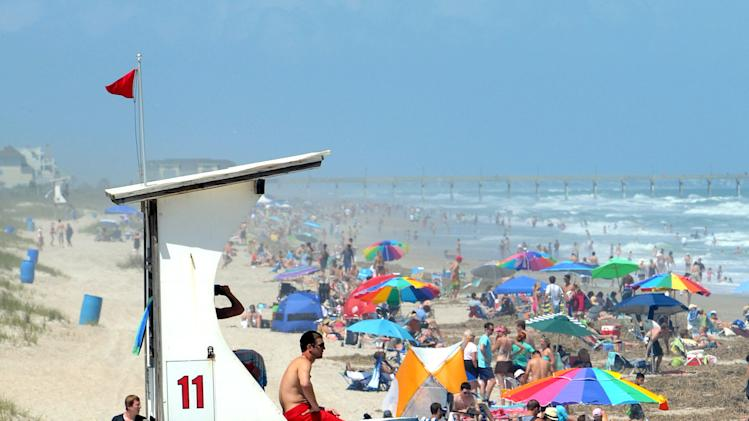People crowd Wrightsville Beach in Wilmington, N.C., as red flags fly warning swimmers of dangerous conditions and rip currents due to Tropical Storm Beryl on Sunday May 27, 2012. The National Hurricane Center in Miami said late Sunday afternoon that Beryl would make landfall in several hours, and that tropical storm conditions were already near the coasts of northeastern Florida and southeastern Georgia. Gusts are possible late Sunday and early Monday. (AP Photo/The Star-News, Jeff Janowski)