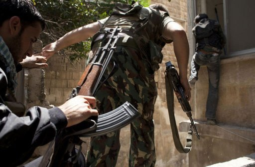 Members of the Free Syrian Army move between two buildings on the outskirts of the Salaheddin neighbourhood of the Syrian city of Aleppo on August 14, 2012. A woman Japanese reporter has been killed while covering clashes in Aleppo