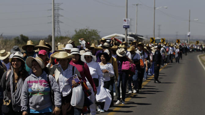 Pilgrims walk along a road toward the site where Pope Benedict XVI will give a Sunday Mass in Bicentennial Park near Silao, Mexico, Saturday March 24, 2012.  Benedict arrived in Mexico Friday afternoon, a decade after the late Pope John Paul II's last visit. The pontiff's weeklong trip to Mexico and then to Cuba on Monday is his first to both countries. (AP Photo/Dario Lopez-Mills)