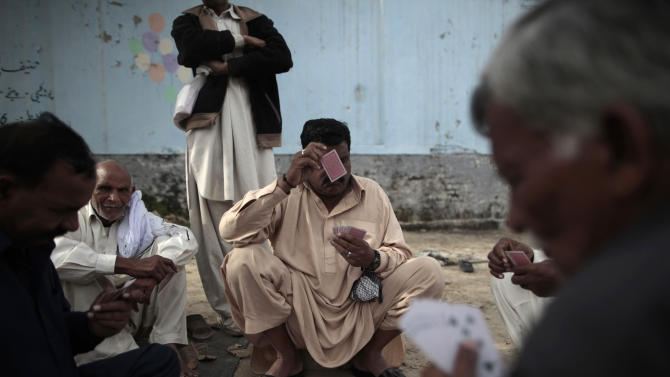"In this Monday, March 18, 2013 photo, Pakistani men play cards in an alley of a neighborhood, in Islamabad, Pakistan. For months, the Supreme Court's Chief Justice Iftikhar Chaudhry has been leading special hearings on Karachi's crime, berating the city's top police officers for failing to act. The past week, he demanded they move in to clean up so-called ""no-go"" areas _ entire neighborhoods where police fear to tread _ according to local press reports. (AP Photo/Nathalie Bardou)"