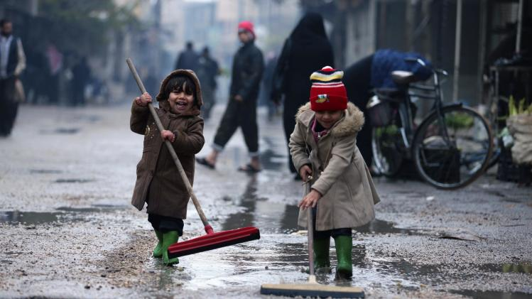 Children remove excess rain water on a street in Duma, Damascus