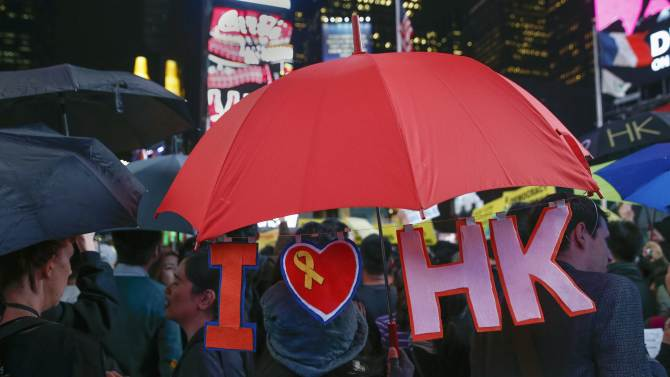 Demonstrators hold umbrellas in support of Hong Kong's pro-democracy marches, at Times Square in New York