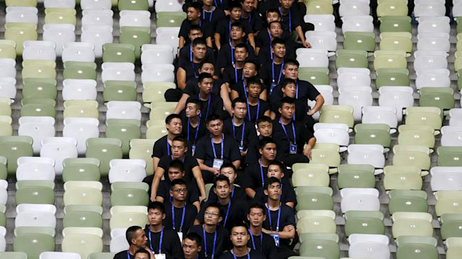 Security guards sit in an empty stand to separate Chinese and Hong Kong fans during their World Cup qualifying match in Shenzhen