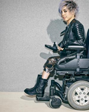 """This undated image provided by Nordstrom shows a model in a wheelchair advertising boots in the company's annual July anniversary catalog, which is its biggest sale event of the year with preview discounts on new fashions for fall. Nordstrom has been using professional models with disabilities in ads and catalogs since 1997. A consulting firm called Global Disability Inclusion says only a few companies use models with disabilities _ though there are more now than in the past _ and calls Nordstrom """"an industry leader"""" in that regard. (AP Photo/Nordstrom)"""