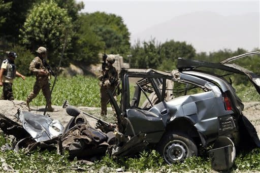 U. S. troops arrive at the site where a vehicle was hit by a remote control bomb in the Khugyani district of Jalalabad province, east of Kabul, Afghanistan on Saturday, July 21, 2012. The bomb killed several civilians and injured two others, including a woman, a local government spokesman said. (AP Photo/Rahmat Gul)