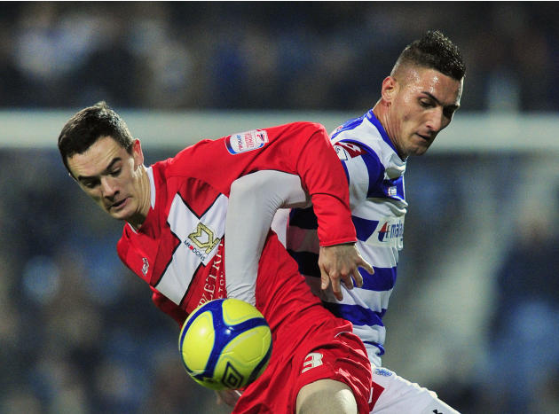 Milton Keynes Dons' Republic of Ireland midfielder Shaun Williams (L) vies with Queens Park Rangers' striker Federico Macheda (R) during their English FA Cup 3rd round replay football match against Qu