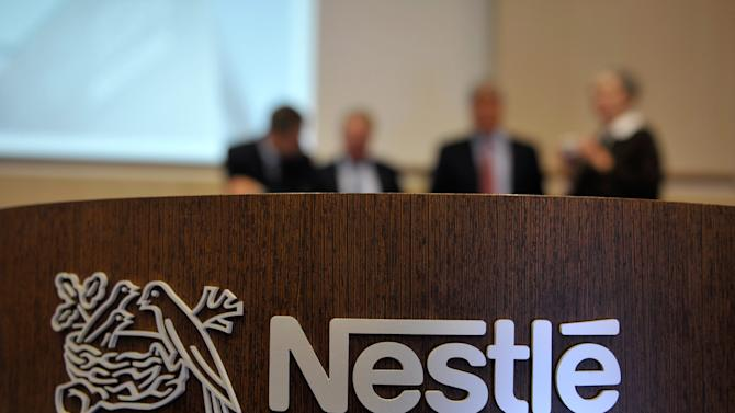 FILE - In this Feb. 19, 2010 file photo people are standing behind a Nestle logo during a press conference of the food and drinks giant Nestle in Vevey, Switzerland. Swiss food and drink giant Nestle SA on Thursday Oct. 18, 2012  posted an 11 percent increase in sales of dozens of its household name brand products for the first nine months of 2012. The world's biggest food and drink company's sales rose to 67.6 billion Swiss francs (US $73.3 billion) through September, up from 60.9 billion francs during the same period in 2011. With 11.7 percent growth in emerging markets and 2.4 percent growth in developed markets, the maker of Nescafe, Jenny Craig and Haagen-Dazs said in a statement issued before the opening of the Zurich exchange Thursday that it expects organic sales growth of 6.1 percent this year and 2.9 percent real internal growth.   (AP Photo/Keystone, Dominic Favre, File)
