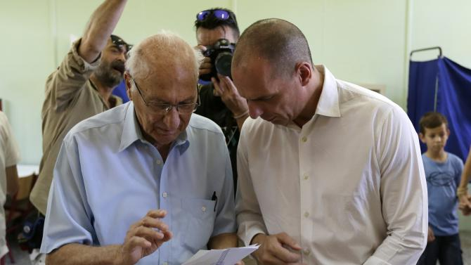 Greece's Finance Minister Yanis Varoufakis, right, and his father Giorgos Varoufakis, 90, prepare to vote at a polling station in Athens, Sunday, July 5, 2015. Greeks were voting Sunday in a bailout referendum that will decide the country's future, with opinion polls showing people evenly split on whether to accept creditors' proposals for more austerity in exchange for rescue loans or defiantly reject the deal. (AP Photo/Petr David Josek)