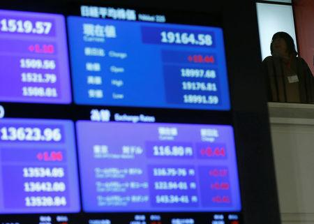 A stock quotation board displaying Japan's Nikkei average is seen before a ceremony marking the end of trading in 2016 at TSE in Tokyo