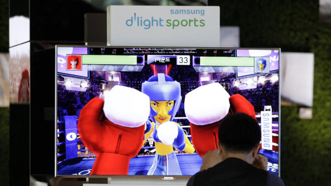 In this Tuesday, June 19, 2012 photo, a visitor plays a boxing game with Samsung Electronics Co.'s  3D television in a showroom at Samsung Electronics Co. headquarters in Seoul, South Korea, South Korean TV manufacturers are making billion dollar bets on a new display technology that promises an even thinner screen and imagery of eye-popping clarity. (AP Photo/Ahn Young-joon)