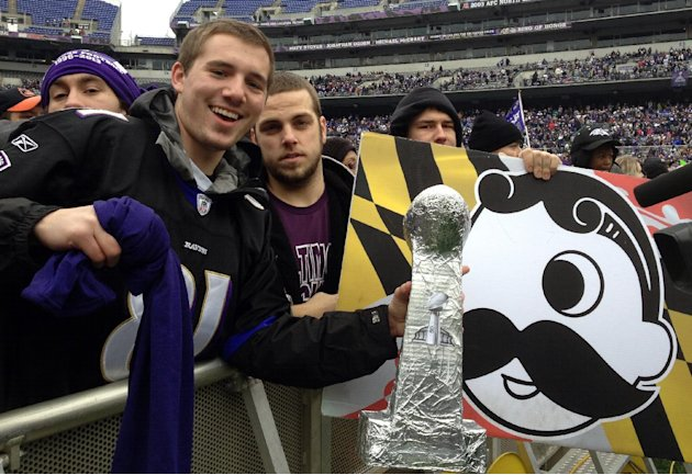 Sam Muffoletto, 21, and Phil Luzi, 21, hold up signs and a home-made Super Bowl trophy as they wait for the start of Baltimore's celebration for the Super Bowl champion Baltimore Ravens at Ravens stad