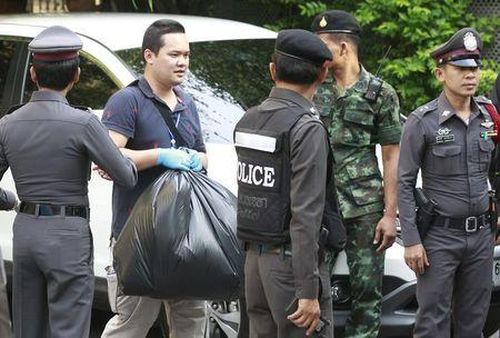 Thai Royal Police officials remove evidence from the site where a suspect of the recent Bangkok blast was arrested, in Bangkok