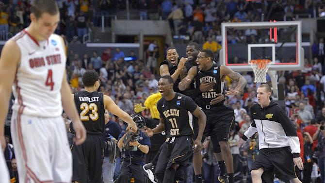 Wichita State players celebrate their 70-66 win over Ohio State in the West Regional final in the NCAA men's college basketball tournament, Saturday, March 30, 2013, in Los Angeles. Ohio State guard Aaron Craft (4) walks off at left. (AP Photo/Mark J. Terrill)