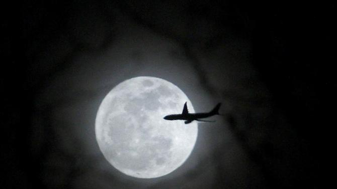 A plane passes in front of a full moon over New York City