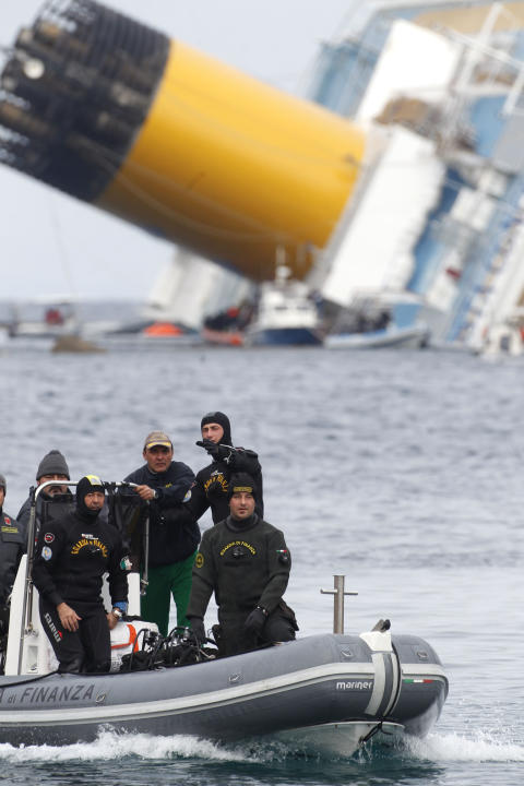 Italian Financial police scuba divers sale around the grounded cruise ship Costa Concordia off the Tuscan island of Giglio, Italy, Friday, Jan. 27, 2012. Costa Crociere SpA offered uninjured passenger