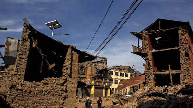Earthquake survivors walk past their collapsed houses in Sankhu, on the outskirts of Kathmandu