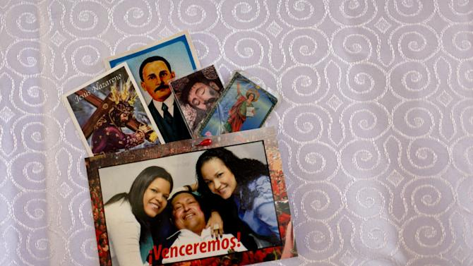 "A postcard of Venezuela's President Hugo Chavez with his daughters; Maria Gabriela, left, and Rosa Virginia, is pinned together with prayer cards to the altar cloth in the military hospital's chapel, in Caracas, Venezuela, Tuesday, March 5, 2013. A brief statement read on national television by Communications Minister Ernesto Villegas late Monday carried the sobering news about the charismatic 58-year-old leader's deteriorating health. Villegas said Chavez is suffering from ""a new, severe infection."" The state news agency identified it as respiratory. (AP Photo/Ariana Cubillos)"