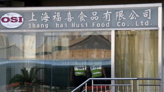 Security guards stand inside the Husi Food factory in Shanghai