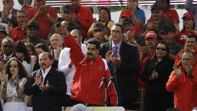 Venezuela's Vice President Nicolas Maduro, center, pumps his fist in the air during a symbolic inauguration for Venezuela's President Hugo Chavez outside Miraflores presidential palace, as National Assembly President Diosdado Caballo, right, looks on in Caracas, Venezuela, Thursday, Jan. 10, 2013.  At left are Nicaragua's President Daniel Ortega and wife Rosario Murillo. The government organized the unusual show of support for the cancer-stricken leader on the streets outside Miraflores Palace on what was supposed to be his inauguration day. Maduro said that even though it wasn't an official swearing-in, Thursday's event still marks the start of a new term for the president following his re-election in October. (AP Photo/Fernando Llano)