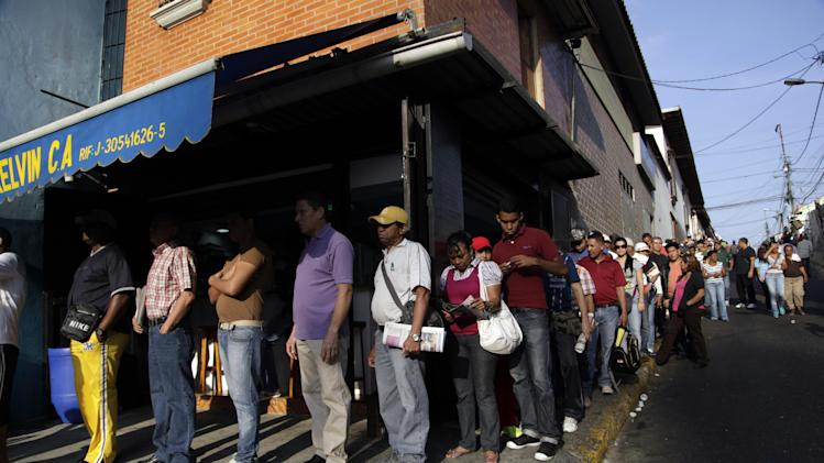 Residents wait in line to enter a polling station to vote in the presidential election in Caracas, Venezuela, early Sunday, April 14, 2013. Interim President Nicolas Maduro, who served as the late President Hugo Chavez's foreign minister and vice president, is running against opposition candidate Henrique Capriles. (AP Photo/Ariana Cubillos)