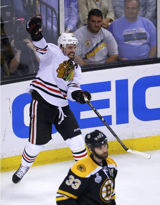 Blackhawks' Sharp celebrates his goal as Bruins' Chara skates away during the third period in Game 4 of their NHL Stanley Cup Finals hockey series in Boston