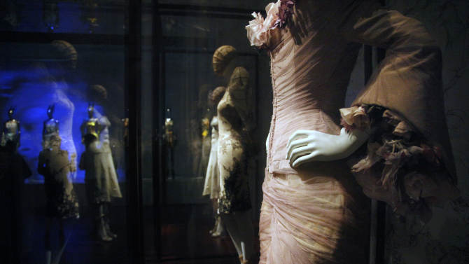 """FILE - In this Monday, May 2, 2011 file photo, designs are seen on display during a press preview of the Alexander McQueen exhibit, """"Savage Beauty,"""" at the Metropolitan Museum of Art, in New York. An exhibition about late fashion designer Alexander McQueen is coming to London, four years after it wowed audiences in New York. The Victoria & Albert Museum says """"Alexander McQueen: Savage Beauty"""" will open in March 2015. (AP Photo/Bebeto Matthews, File)"""