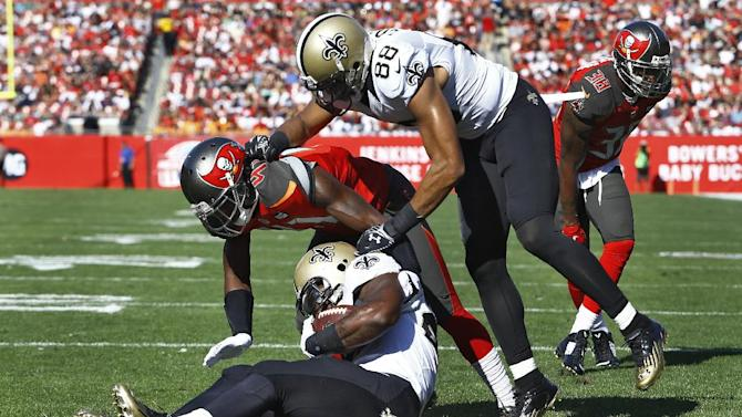 New Orleans Saints running back Khiry Robinson (29) goes into the end zone with a 1-yard touchdown run as teammate wide receiver Nick Toon (88) blocks Tampa Bay Buccaneers defensive back C.J. Wilson (41) during the second quarter of an NFL football game Sunday, Dec. 28, 2014, in Tampa, Fla. (AP Photo/Brian Blanco)