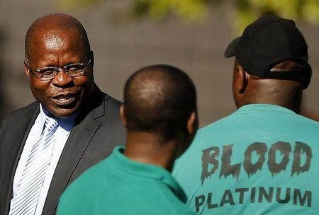 Lonmin Chief Executive Magara looks on after accepting memorandum from striking miners outside Lonmin's headquarters in Johannesburg