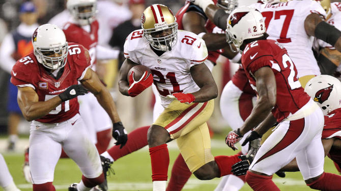 San Francisco 49ers running back Frank Gore (21) tries to gain yardage as Arizona Cardinals cornerback William Gay (22) and Paris Lenon (51) defend during the first half of an NFL football game, Monday, Oct. 29, 2012, in Glendale, Ariz. (AP Photo/Paul Connors)