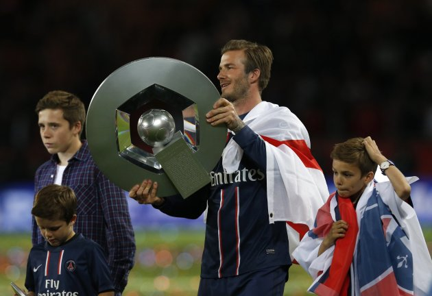 Paris Saint-Germain Beckham raises the French Championship trophy at the end of their team's French Ligue 1 soccer match in Paris