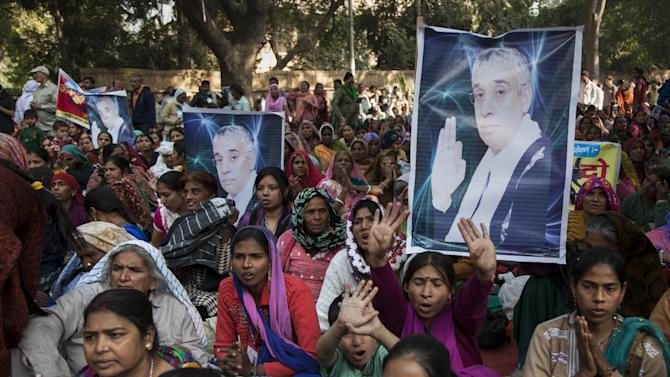Supporters of controversial Indian guru Sant Rampal displaying his photographs, chant slogans praising him as they gather to show support at a protest venue near the Indian Parliament in New Delhi, India, Tuesday, Nov. 18, 2014. In the neighboring Haryana state's Hisar district, several supporters were injured on Tuesday after police searching for Rampal stormed an ashram where he was believed to be holed up. The guru, had repeatedly ignored court summons to appear for questioning in the 2006 killing of a villager by his supporters. (AP Photo/Tsering Topgyal)
