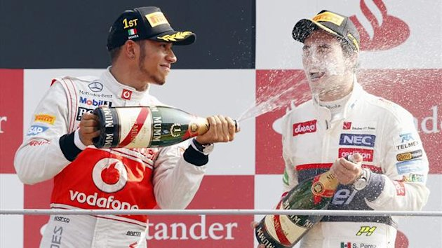 McLaren Formula One driver Lewis Hamilton (L) of Britain sprays champagne on the podium with second-placed Sauber Formula One driver Sergio Perez of Mexico, after the Italian F1 Grand Prix at the Monza circuit (Reuters)