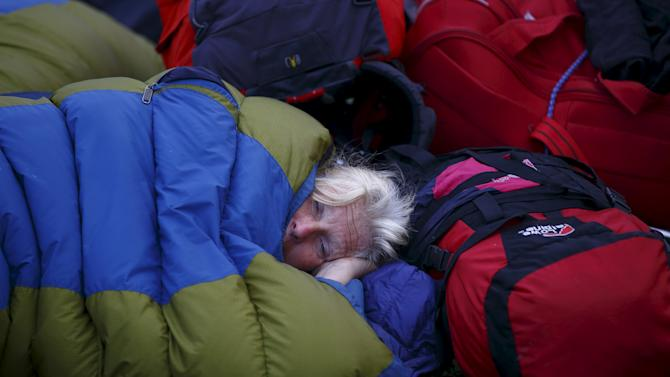 A tourist from the Netherlands waiting for her flight sleeps in a sleeping bag at Tribhuvan International Airport