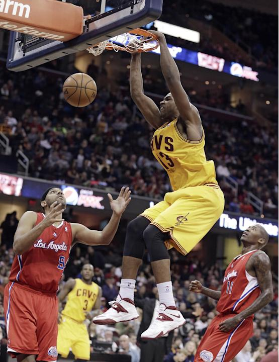 Cleveland Cavaliers' Tristan Thompson (13), from Canada, dunks the ball in front of Los Angeles Clippers' Jared Dudley (9) and Jamal Crawford (11) during the second quarter of an NBA basketbal